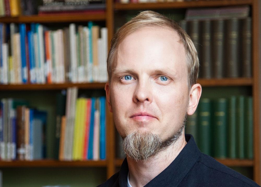 Jonas Ahlskog tittar rakt i kameran. Platsen är SFV:s bibliotek.