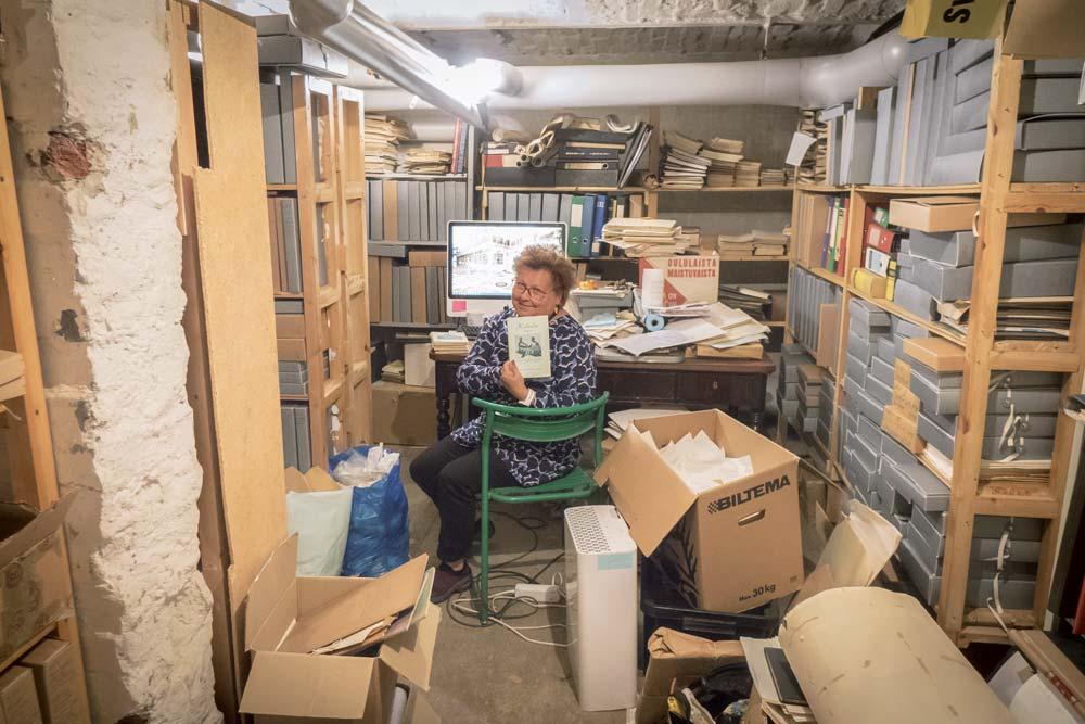 Christina Snellman i SFV:s källararkiv bland dammiga mappar.