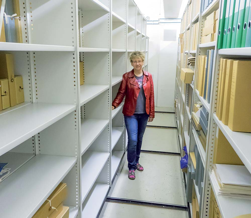 Lena Karhu bland tomma arkivhyllor på Centralarkivet