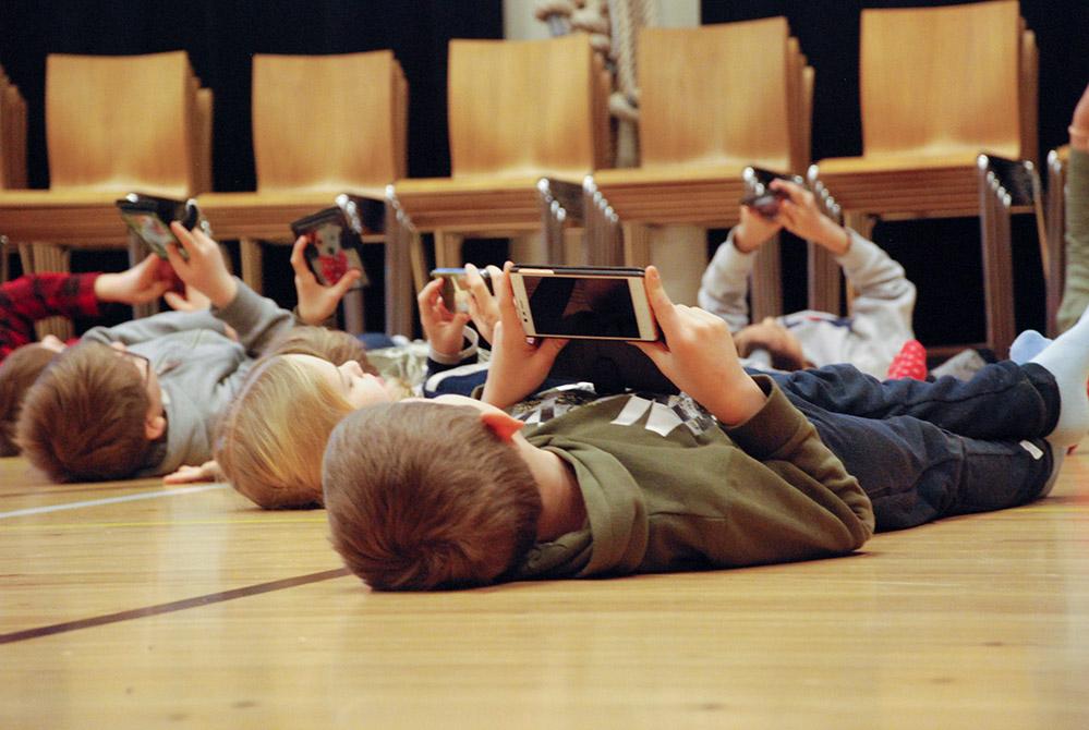 BArnopera: barn på golvet med telefoner